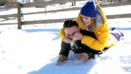 Young Woman in Bright Yellow Coat with Charming Smile is Looking at Handsome Bearded Man Lying on White Snow. Portrait of a Happy Couple Having Fun During Winter Time. Honeymoon and Vacation Concept video
