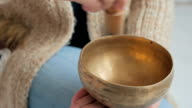 Young woman in cardigan relaxing with nepal singing bowl video
