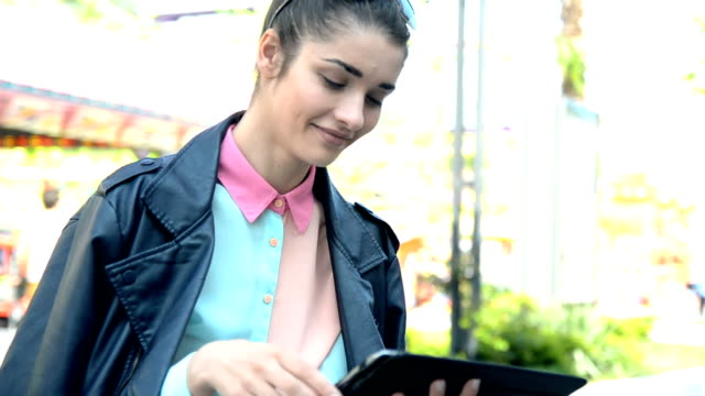 Young woman in city with tablet PC video