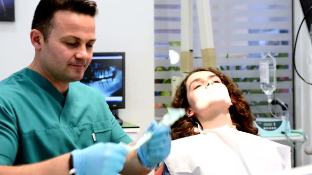 DOLLY: Young woman in dentist office video