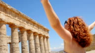 young woman in front of a monument in Sicily: Italy video