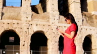 Young woman in front of Colosseum with smart phone in hands in Rome, Italy. Girl in Europe vacation video