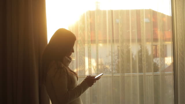 Young woman in front of the window texting. video