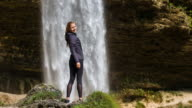 Young woman in front of waterfall looking back and smiling video