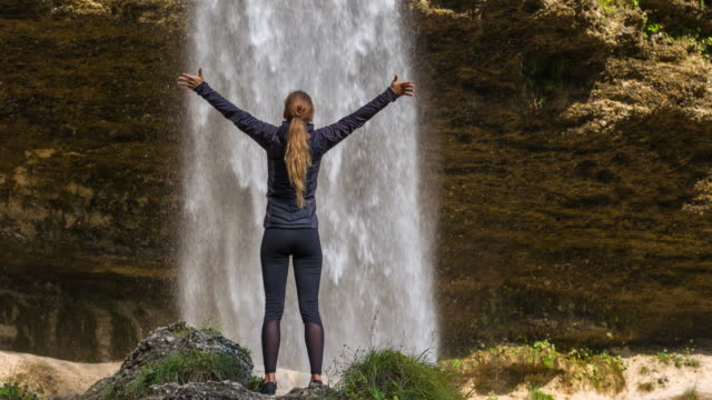 Young woman in front of waterfall with her arms outstretched video
