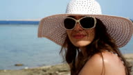 young woman in glasses and a hat on a beach near the sea video