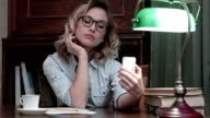 Young woman in glasses making selfies on the phone at her workplace video
