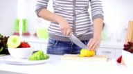 Young woman in kitchen chopping pepper video
