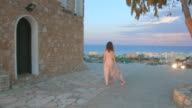 Young woman in long dress walking down the sidewalk to enjoy amazing sea view video