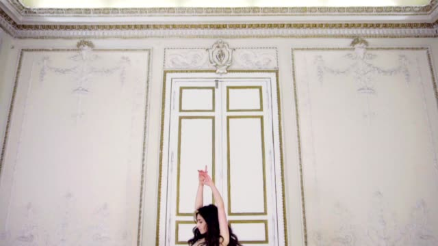 Young woman in long evening dress dances in a hall near the door video