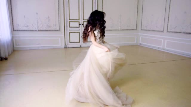 Young woman in long evening dress dances in a hall video