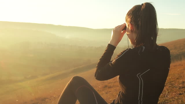 Young woman in nature exploring the hills with the binocular. video
