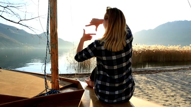 Young woman in nature framing mountain lake landscape with fingers video