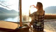 Young woman in nature making heart shape finger frame video