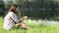 Young woman in nature seated on grass smell mint leaves on lake shore in sunny summer day outdoor - HD video footage video