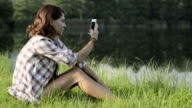 Young woman in nature seated on grass take photo with smartphone on lake shore in sunny summer day outdoor - HD video footage video