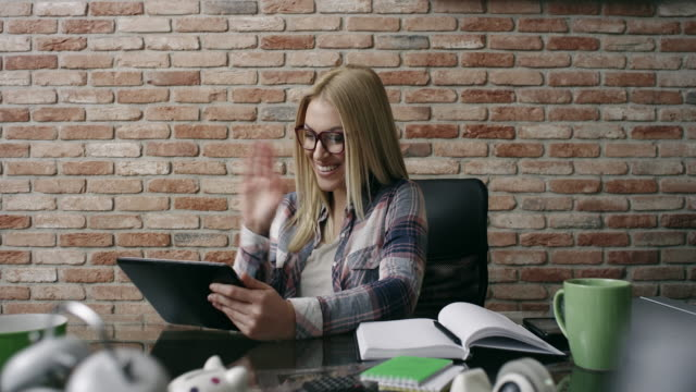 Young woman in office using digital tablet video