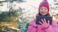 Young woman in pink winter clothes enjoys the tablet. She stands in a winter forest, behind the sun shines beautifully video