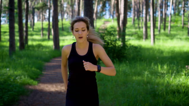 Young woman in sportswoman running down road in summer forest video