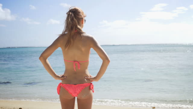 Young woman in swimsuit on beach soaking up summer sun video