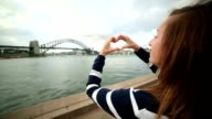 Young woman in Sydney harbour makes heart shape finger frame video