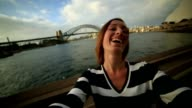 Young woman in Sydney harbour, takes a selfie portrait video