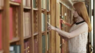 TU DS Young woman searching book on shelf using tablet video