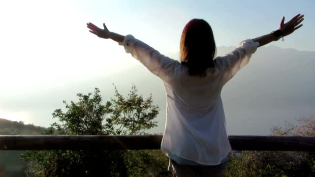 Young woman in the morning with arms outstretched, outdoors video