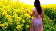 Young Woman in Vintage Dress Walking Down Yellow Spring Path video