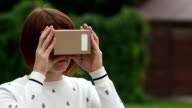 Young Woman in Virtual Reality Glasses cardboard. VR video