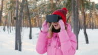 Young woman in virtual reality glasses. In the snow-covered forest, looking around: catching snowflakes. Winter fun and technologies video