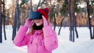 Young woman in virtual reality glasses. In the snow-covered forest, looking around: catching snowflakes video