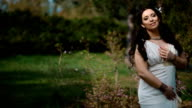 Young woman in white dress in spring park video