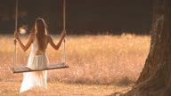 SLO MO TD Woman in white dress swinging under tree video