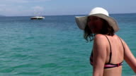 Young woman in white hat relaxing on the beach video