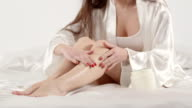 Young woman in white satin robe applying cream on her legs while sitting on the bed video
