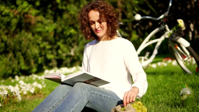 Young woman in white shirt and blue jeans is reading a book sitting on the grass in park and eating grapes. Her city bicycle with basket and flowers is standing behind video