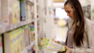Young woman is choosing a corn flakes in the supermarket. video