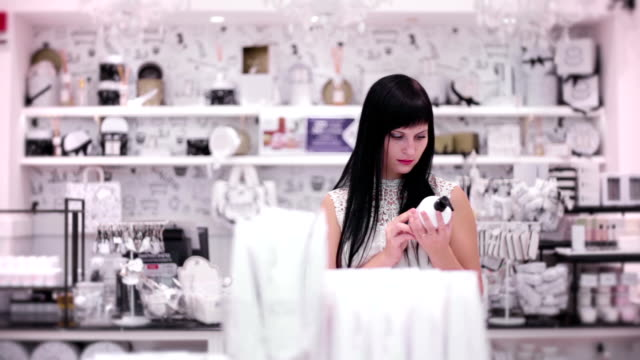 Young woman is choosing a purchase in the cosmetic store video