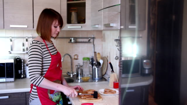 Young woman is cooking in the kitchen video