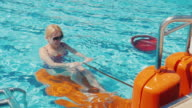 Young woman is exercising on a simulator in the pool. Active rest on fresh air, activity in the resort video