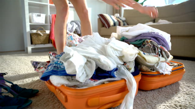A young woman is haphazardly packing and trying to close the chock-full orange suitcase video