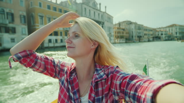 A young woman is photographing herself against the background of buildings on a canal in Venice. Tourism in Italy video