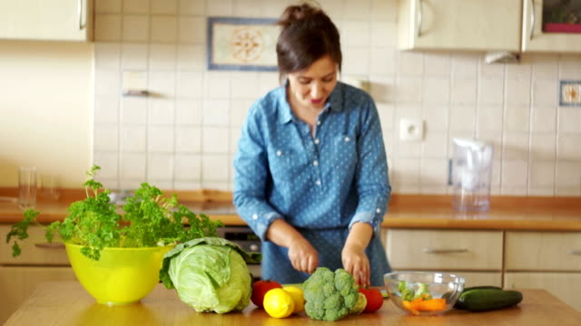 A young woman is preparing a soup dancing between a stove and a table. Great mood. Home kitchen. Vegetarianism. Healthy eating video