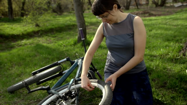 A young woman is repairing a bicycle outdoors. video