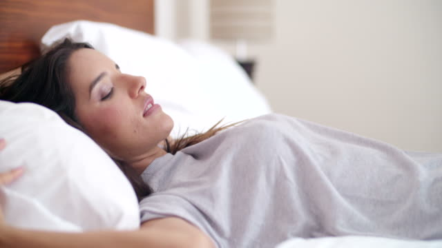Young woman is sleeping on white linen in bed at home video