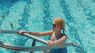 Young woman is training the body in the pool. Aqua gymnastics in the open air, healthy and active lifestyle video