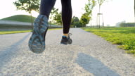 SLOW MOTION CLOSE UP: Young woman jogging in beautiful tree avenue in evening video