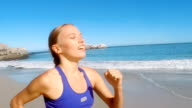 Young woman jogging on beach video