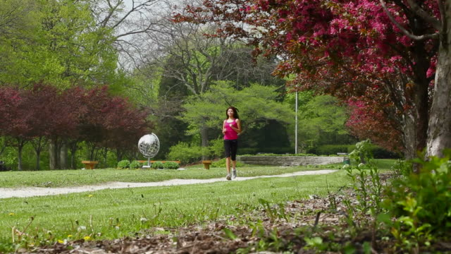 Young woman jogging through the park, dolly shot video